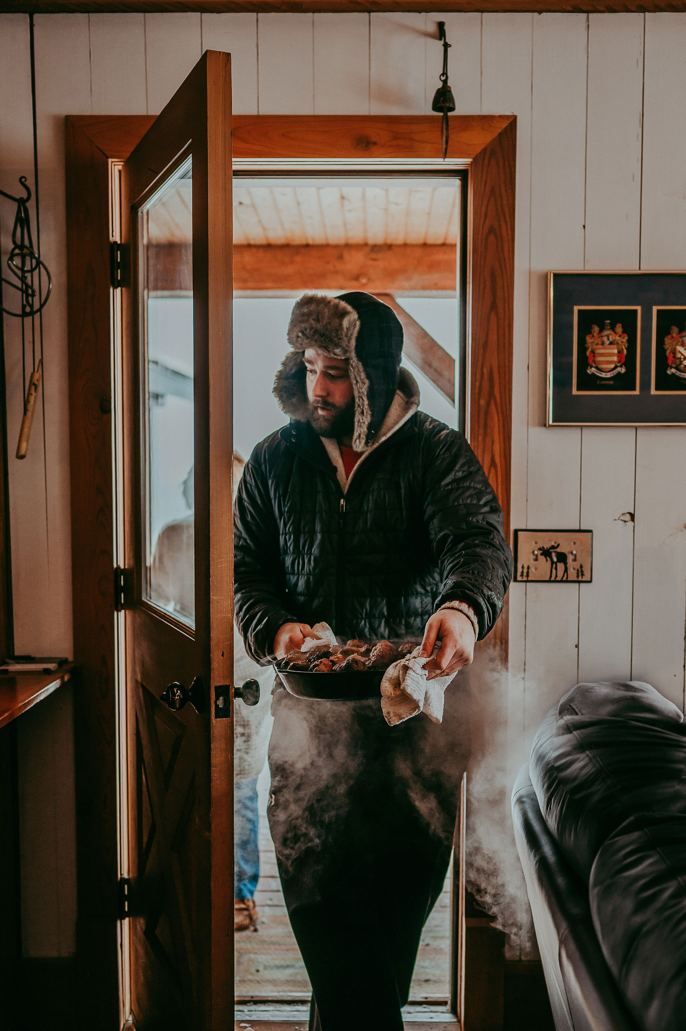 A chef brings hot food in from the cold for a long table dinner