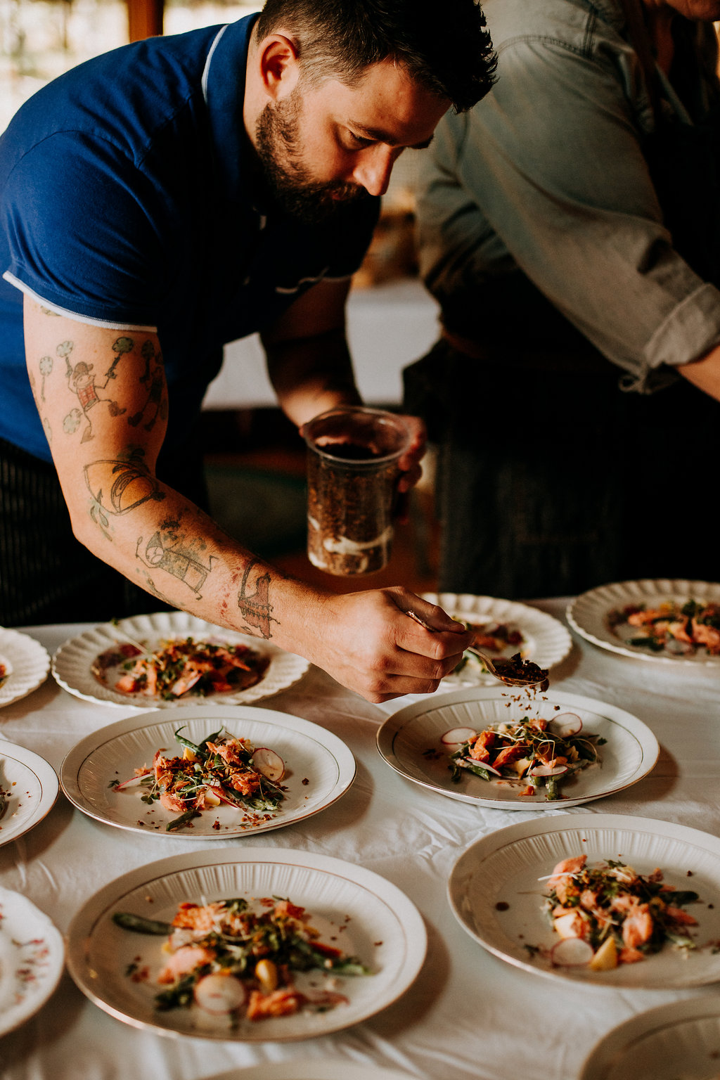 A chef puts the finishing touches on a plated meal for a long table dinner in Calgary