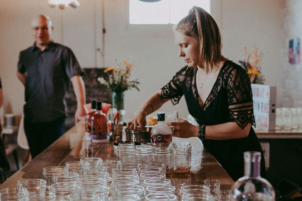 A blonde woman with a ponytail pours drinks into mason jars