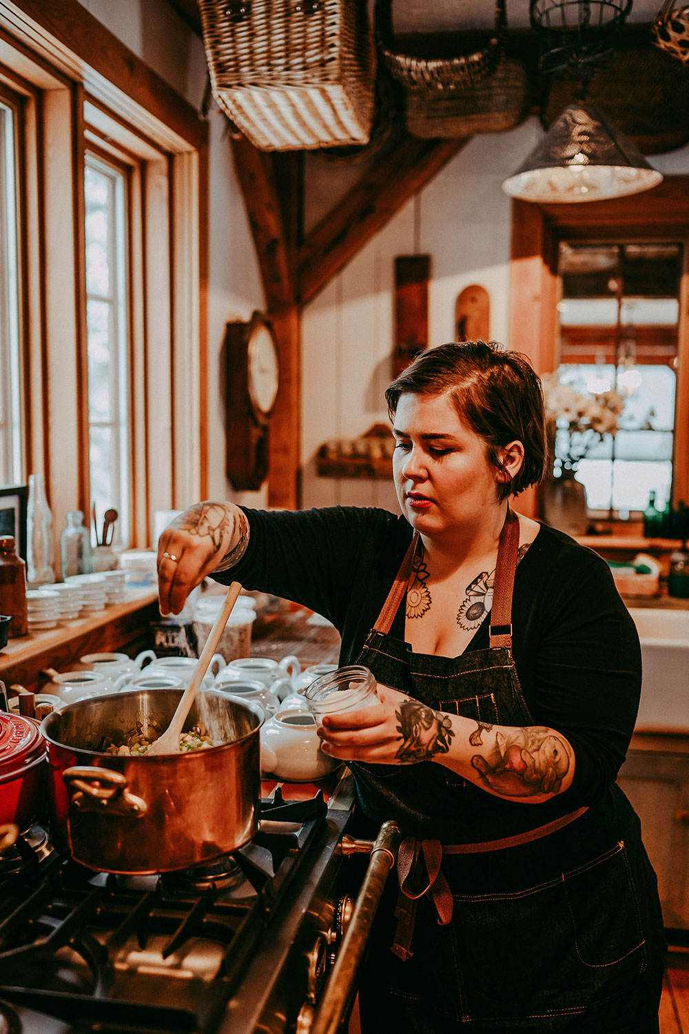 A female chef with tattoos prepares food