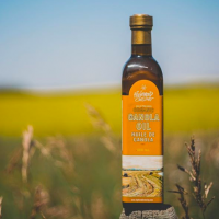 Local canola oil with an orange label on a fence post in a field