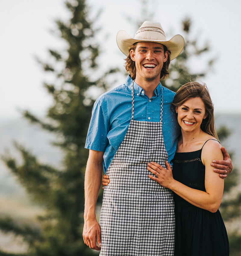 A cowboy and his wife stand in in front of a spruce tree