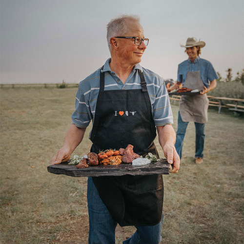 A man with grey hair carries a tray of meat in an apron